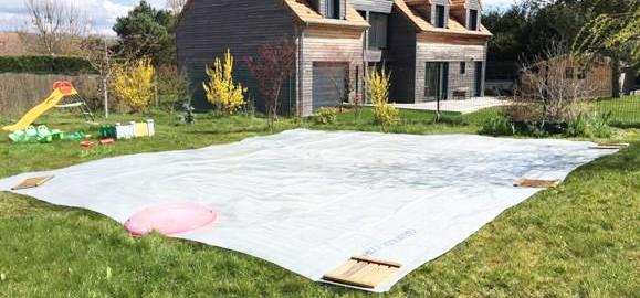 Déplier la bâche au sol permet de mieux la découper.